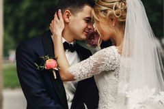 Happy sensual handsome groom and blonde beautiful bride in white. Dress hugging Royalty Free Stock Image