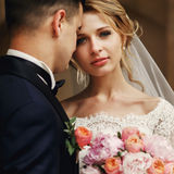 Happy sensual handsome groom and blonde beautiful bride in white. Dress hugging  close-up Stock Image