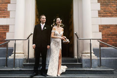 Happy sensual sexual bride and handsome groom outside church thr Royalty Free Stock Photo