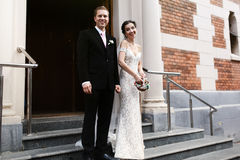 Happy sensual sexual bride and handsome groom outside church thr Stock Image