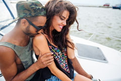 Happy sensual young couple kissing and embracing on boat royalty free stock photo