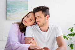 Happy sensual young couple in pajamas sitting together. At home royalty free stock photo