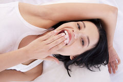 Happy sensual young woman lying in bed Stock Images