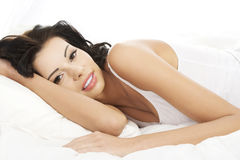 Happy sensual young woman lying in bed Stock Image