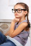 Happy serious calm kid girl in eyeglasses looking and thinking a. Bout with fun face. Closeup portrait Royalty Free Stock Images