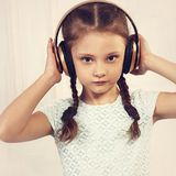 Happy serious kid girl in blue dress listening the music in wire Stock Photo
