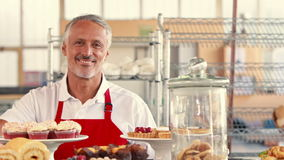 Happy server looking at camera with thumbs up behind cakes stock video footage