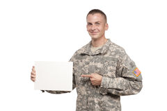 Smiling soldier points to a blank sign Royalty Free Stock Photo