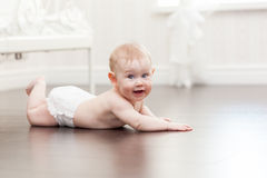Happy seven month old baby girl crawling on a hardwood floor. In living room Stock Images