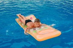 Happy seven year old boy lying on air mattress in outdoor pool stock image
