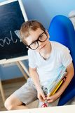 Happy seven years old boy holding his school supplies. Stock Photo