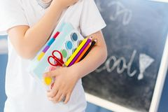 Happy seven years old boy holding his school supplies. Royalty Free Stock Images