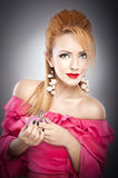 Happy sexy beautiful blond girl in pink dress with hairstyle and bright makeup and perfume bottle Royalty Free Stock Image