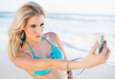 Happy sexy blonde in bikini taking a self picture Stock Photography