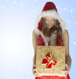 Happy sexy christmas girl holding gift box. Xmas portrait of very sexy lady with long hair, sexy dress and fur hood smiling and looking the pretty gift box  with Royalty Free Stock Image
