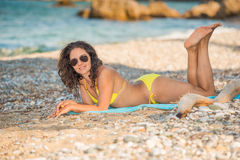 Happy sexy girl. Beautiful girl posing on the beach in sunglasses and yellow bikini smiling looking at the camera Royalty Free Stock Photo