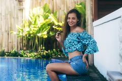 Happy sexy girl in denim shorts and top sits on pool. Young tanned model resting on summer day. Concept vacation stock image