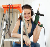 Happy sexy girl  in headphones  with drill Stock Image