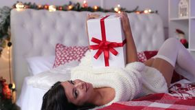 Portrait of a sexy girl with Christmas gift on bed stock footage