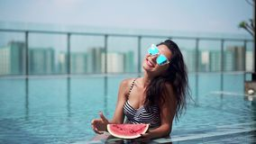 Happy sexy girl with watermelon in pool stock video