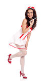 Happy sexy nurse holding a syringe. Full body shot of a sexy beautiful young nurse wearing red high heels shoes holding a syringe  and smiling on isolated white Stock Photo