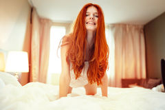 Happy redhead woman on bed Stock Images