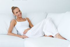 Happy Sexy Woman Leaning at White Couch. Happy Sexy Woman in White Outfit Leaning at White Couch. Captured Indoor on White Wall Background Royalty Free Stock Photography