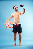 Happy shirtless guy holding beach ball and making selfie Stock Photos