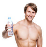 Happy shirtless sportsman holds water. Stock Image