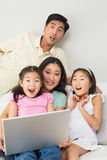 Happy shocked family of four using laptop Royalty Free Stock Images