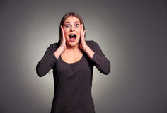 Happy shocked young woman. Emotional portrait of happy shocked young woman over dark background Stock Photos