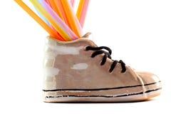 Happy shoe. Ceramic shoe with colorfull straws, white background Royalty Free Stock Image