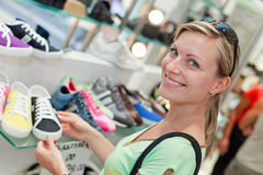 Happy shoe shopping girl. Smiling blonde girl shopping for colourful sporty shoes Royalty Free Stock Photos