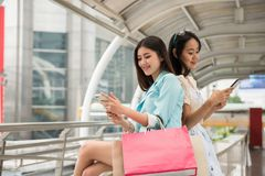 Shopaholic friends play smartphone in city. Happy shopaholic beautiful friends browsing retail stores location by 4g internet from smartphone or play social stock images
