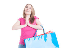 Happy shopaholic with colorful shopping bags praying Stock Photography