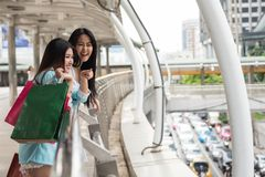 Happy shopaholic friends shopping in town. Happy shopaholic friends look for shopping mall in town. Two beautiful young Asian women enjoying summer discount sale Royalty Free Stock Photo