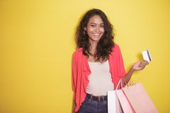 Happy shopaholic with shopping bag and credit card. Portrait of happy shopaholic with shopping bag and credit card on yellow background Stock Photo