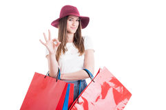 Happy shopaholic showing ok symbol and carrying shopping bags Royalty Free Stock Photography
