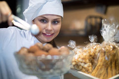 Happy shopgirl working with different pastry Royalty Free Stock Images