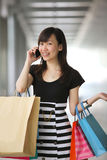 Happy Shopper. Smiling with Shopping Bags on Phone stock images