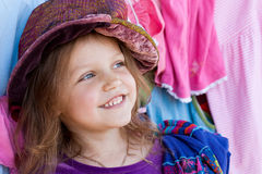 Happy shopper. Happy little girl with clothes Royalty Free Stock Images