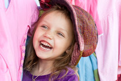 Happy shopper. Laughing little girl wearing colorful hat Stock Images