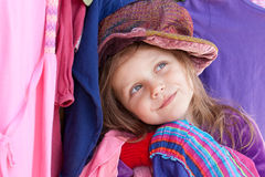 Happy shopper. Little girl with clothes  wearing colorful hat Royalty Free Stock Images
