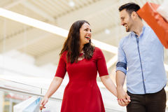 Happy shopper couple buying clothes. In shopping center stock photography