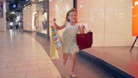 Happy shopper girl with paper bags in hurry to get discount in boutiques. At mall stock video footage