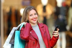 Happy shopper holding bags and phone looking at camera. Happy shopper holding shopping bags and smart phone looking at camera in a commercial centre stock images