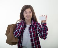 Happy shopper holding discount white card and shopping bags and carton boxes in her hands. Young girl with credit card. stock photography