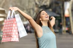 Happy shopper holding shopping bags in a street. Happy shopper holding shopping bags raising arms in a street stock photography