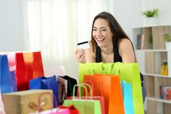 Happy shopper looking at multiple purchases stock photography