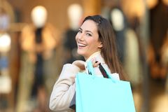 Happy shopper looking at you in a mall. Portrait of a happy shopper holding blank shopping bags looking at you in a mall in winter Royalty Free Stock Photo